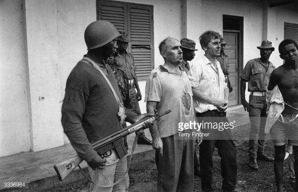 21st May 1968: John Downing-Tractor, a company rep, and William Blakeley, a marine manager, under guard by Nigerian Federal troops who took them hostage when they captured Port Harcourt during the Biafran War. (Photo by Terry Fincher/Express