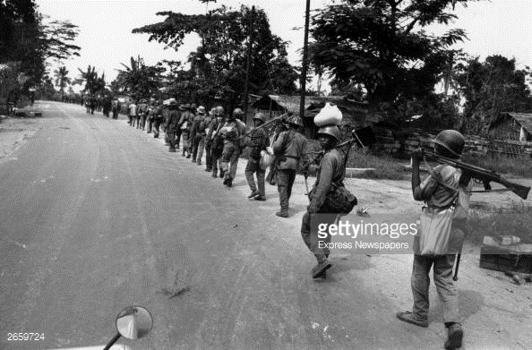 Troops from the Nigerian Federal Army marching along a road after routing Biafran troops at Port Harcourt during the Biafran War.