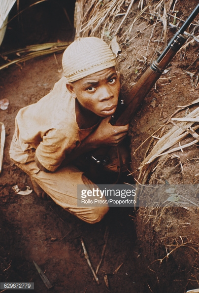 View of a young male soldier from the Republic of Biafra crouching in a foxhole with a rifle during the Nigerian - Biafran civil war in Nigeria in August 1968. Members of the Igbo tribe rebelled in 1967 to demand a separate Republic of Biafra. The war and famine lasted until 1970, when the Biafran Republic forces surrendered to the nationalist government.